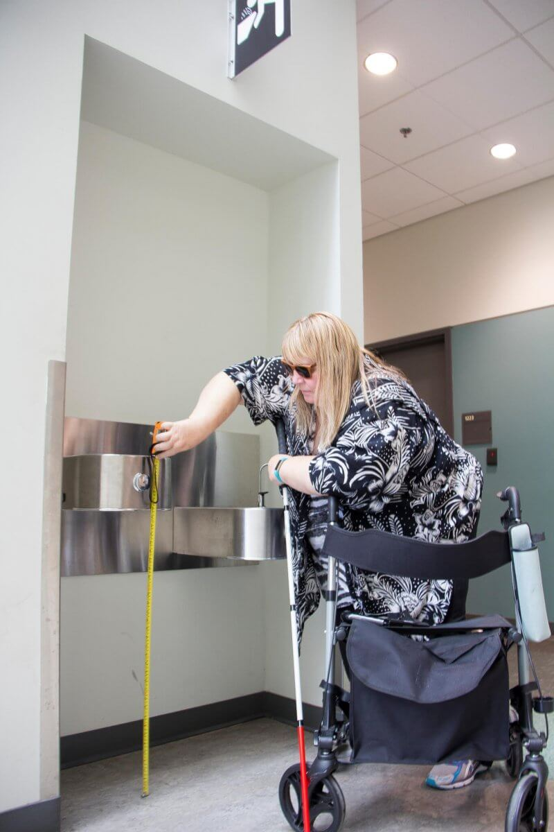A woman is shown taking a measurement to determine accessibility in a building.