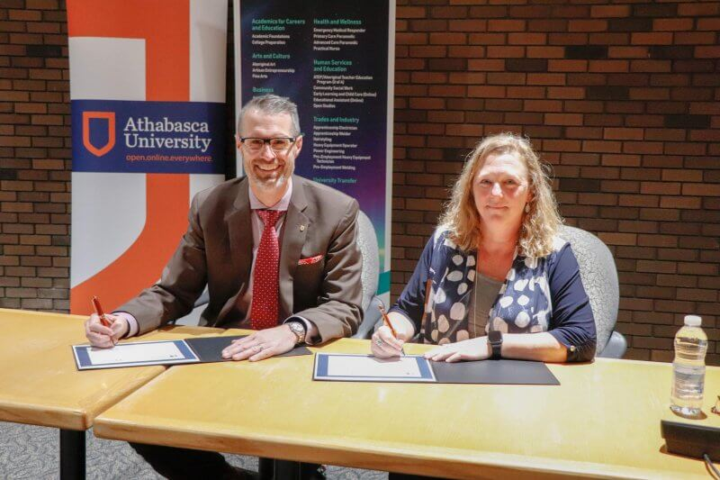 Athabasca University President Dr. Neil Fassina and Portage College President Nancy Broadbent signing a Memorandum of Action to strengthen the partnership between the two institutions.