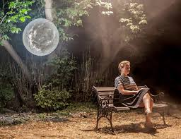 Woman sitting on a bench in a forest setting with a small moon floating behind where she sits