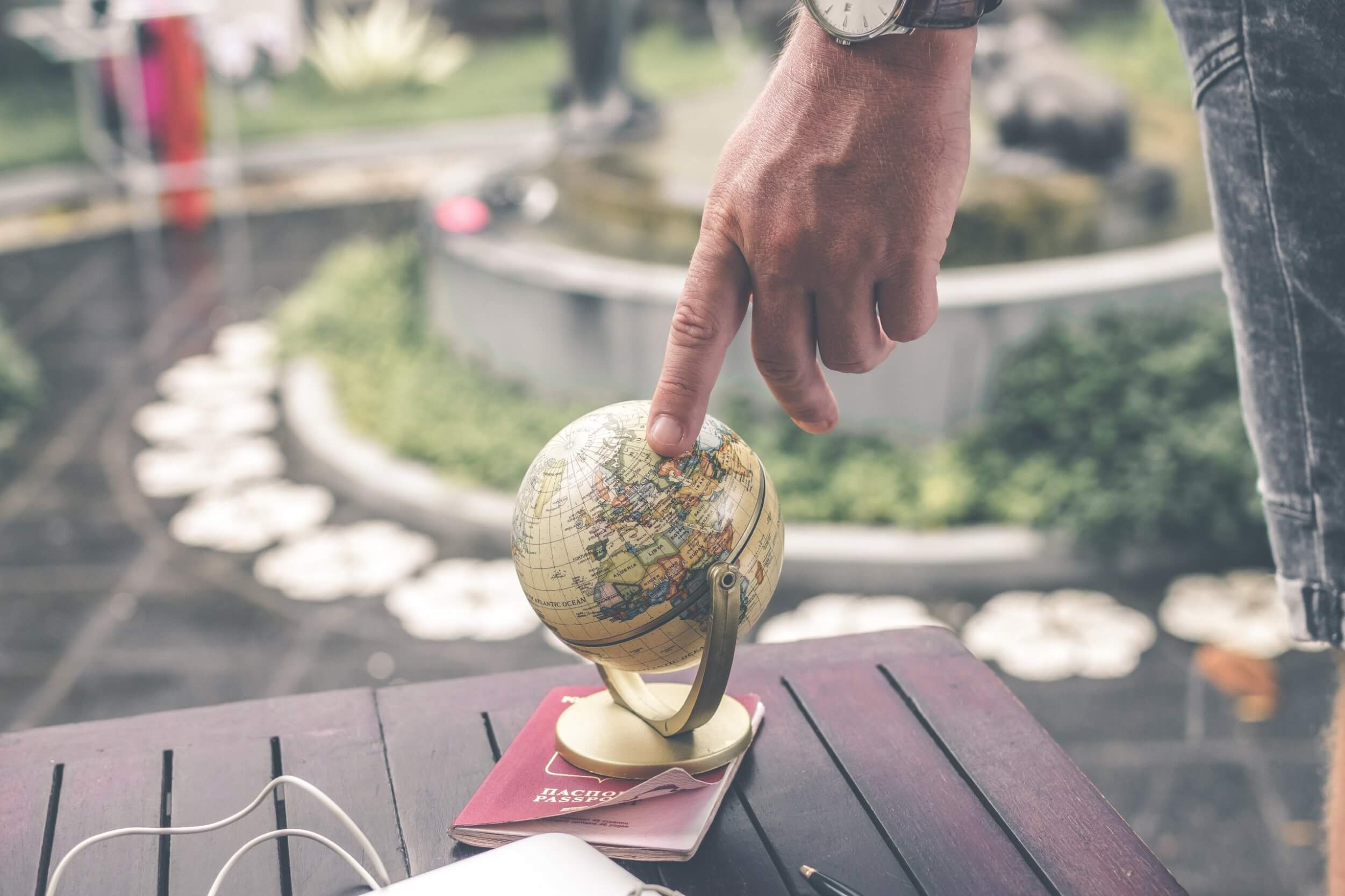 Person with their finger on a small globe