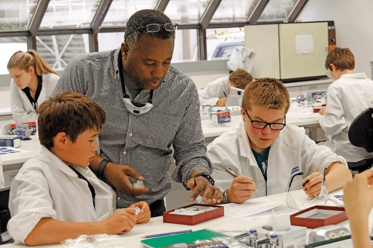 Dr. Ken Munyikwa of Athabasca University discussing rocks and minerals with school children in AU's teaching laboratory in Athabasca. Photo: R.G. Holmberg.