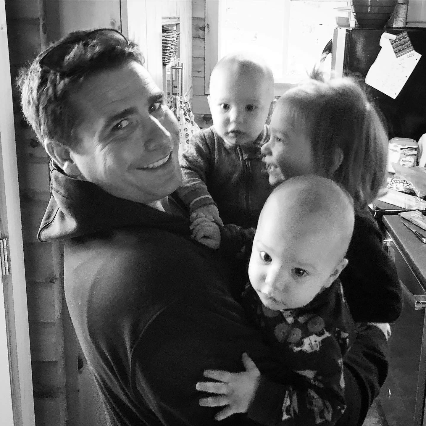 Thompson with his three young children all being held in his arms