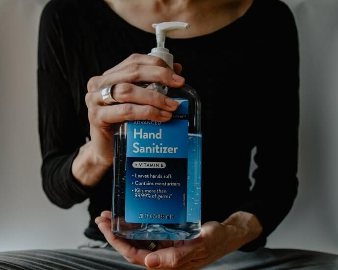 A closeup shot of hands holding a bottle of hand sanitizer.