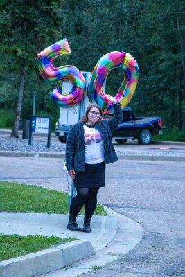 AUSU president holding 50 balloons