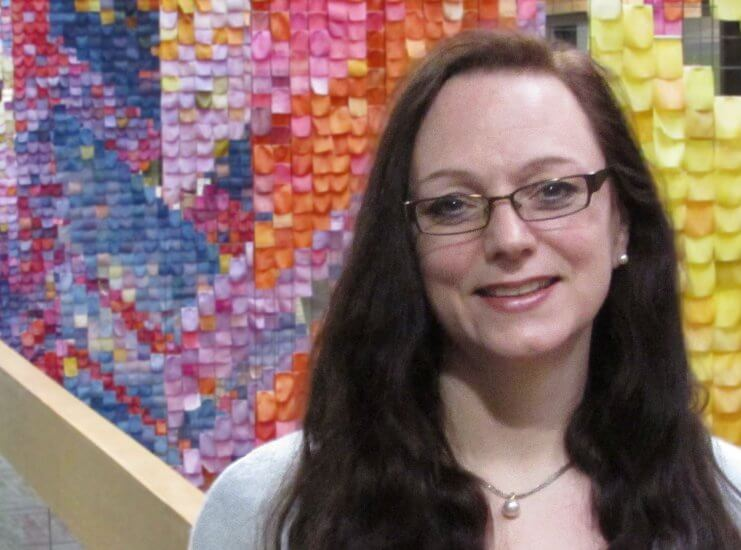 Peggy Lynn MacIsaac in front of a colourful mosaic
