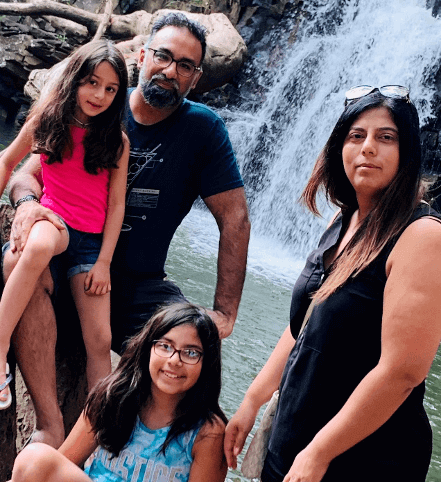 Robbie Madan with his wife and two daughters in front of a waterfall