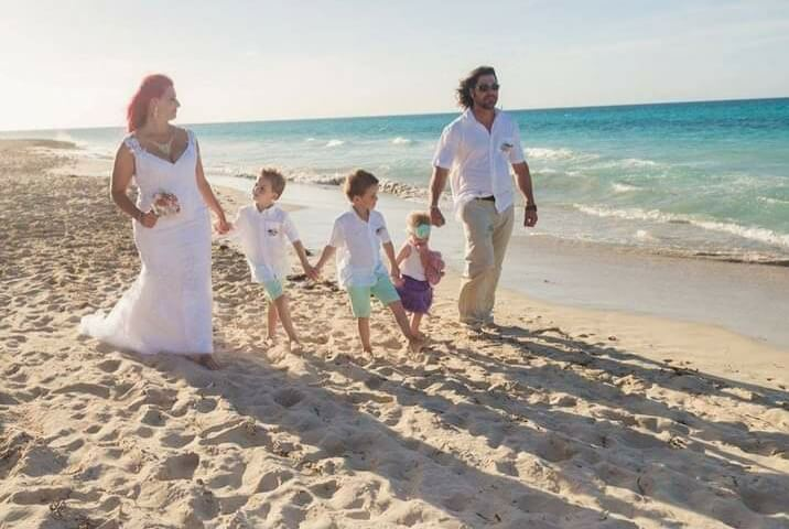 Megan Maksym on the beach wearing a wedding dress holding the hand of one her sons' who's holding hands with his brother, who's holding hands with his sister, who's hands with Megan's husband who is wearing a white colloared t-shirt and khaki pants
