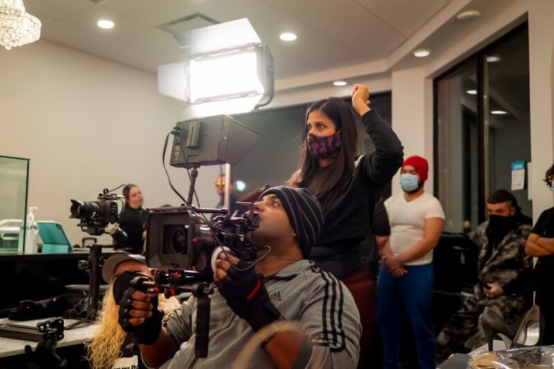 Cast wearing masks filming in a room