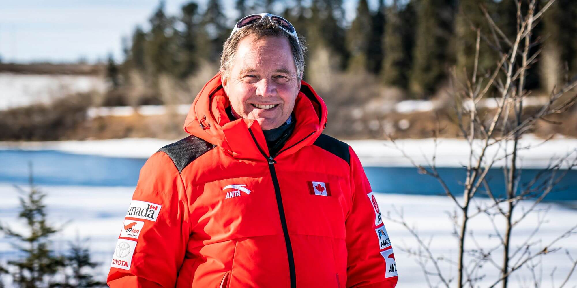 Todd Allison wearing a bright red winter jacket standing infront of a frozen river with pine trees behind it