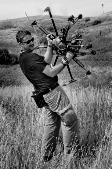 A black and white photo of Dave Blaine holding a camera drone