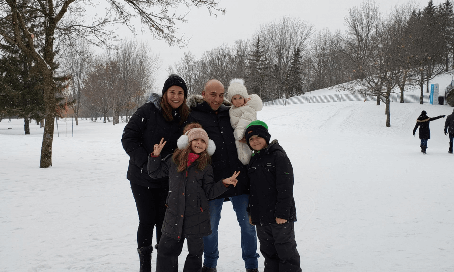 AU student with his family standing together on a snowy day
